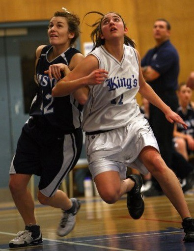 Two women boxing out during a basketball game