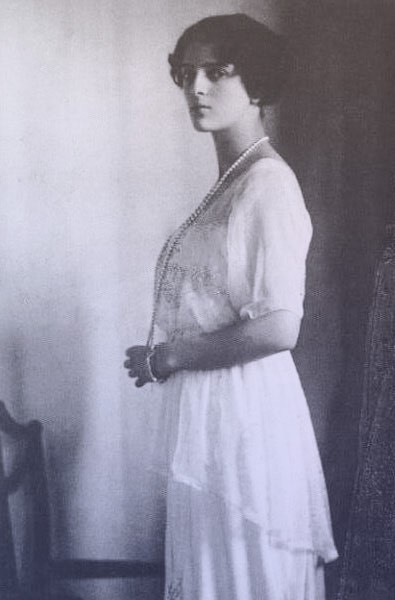 Princess Irina Alexandrovna in profile, wearing a white day dress with a long pearl necklace.