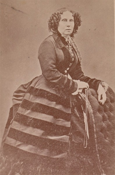 Sophie posing beside a chair, wearing a dark day dress with long sleeves and tiered skirt.