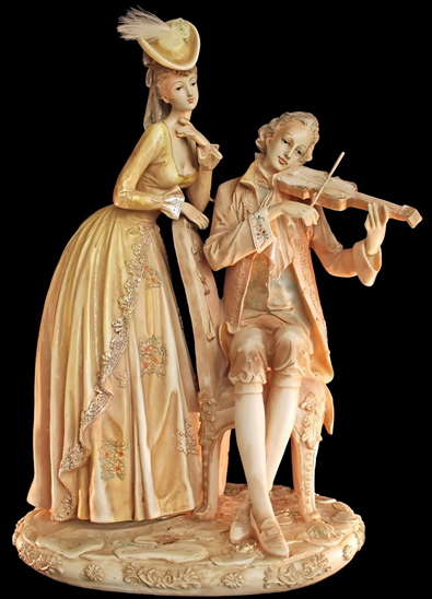 Image of two Victorian statuettes. A female in a full-skirted gown is standing and listening to a seated male violinist.