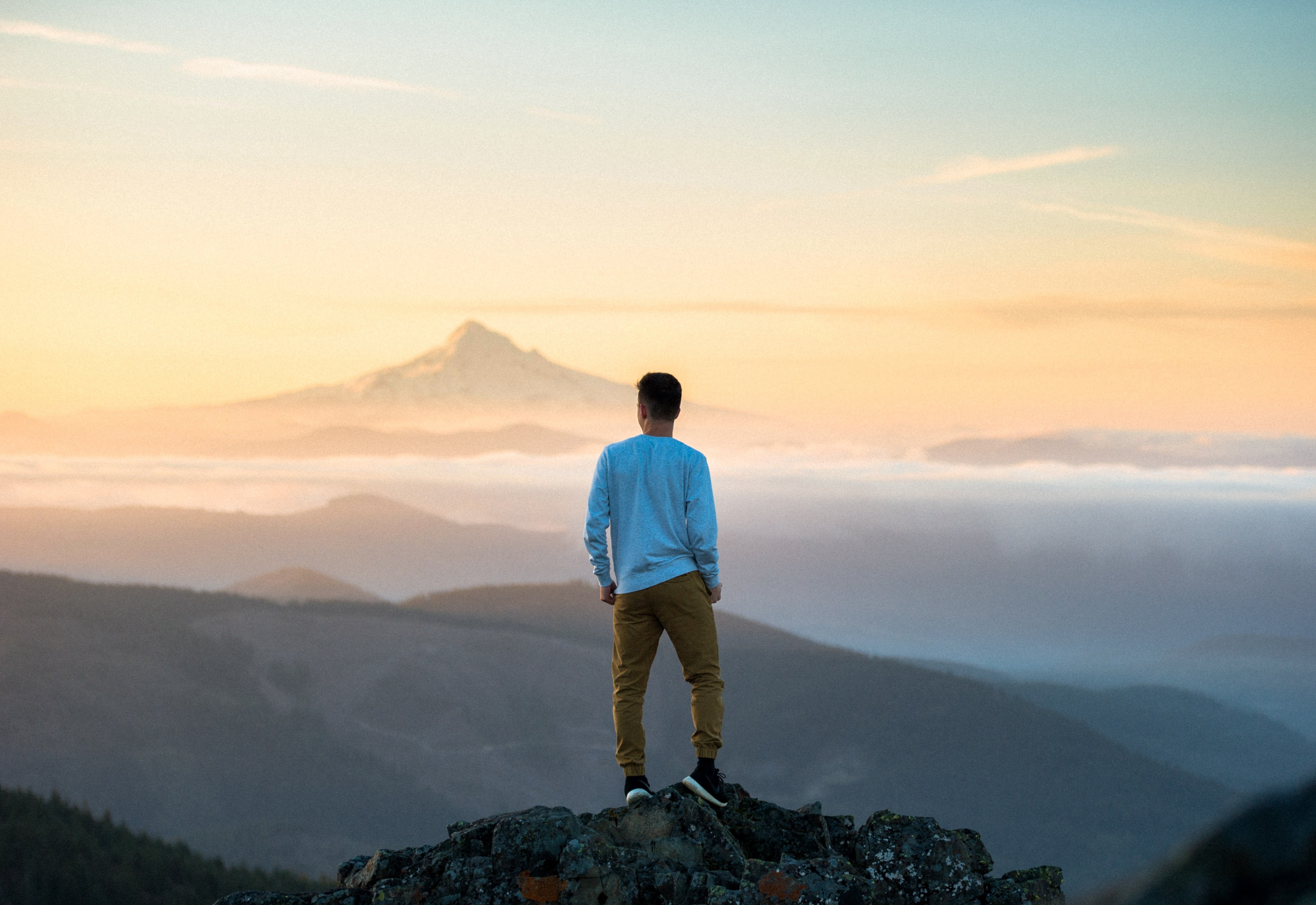 man wearing light blue top standing on top of hill overlooking mountains and foggy valley
