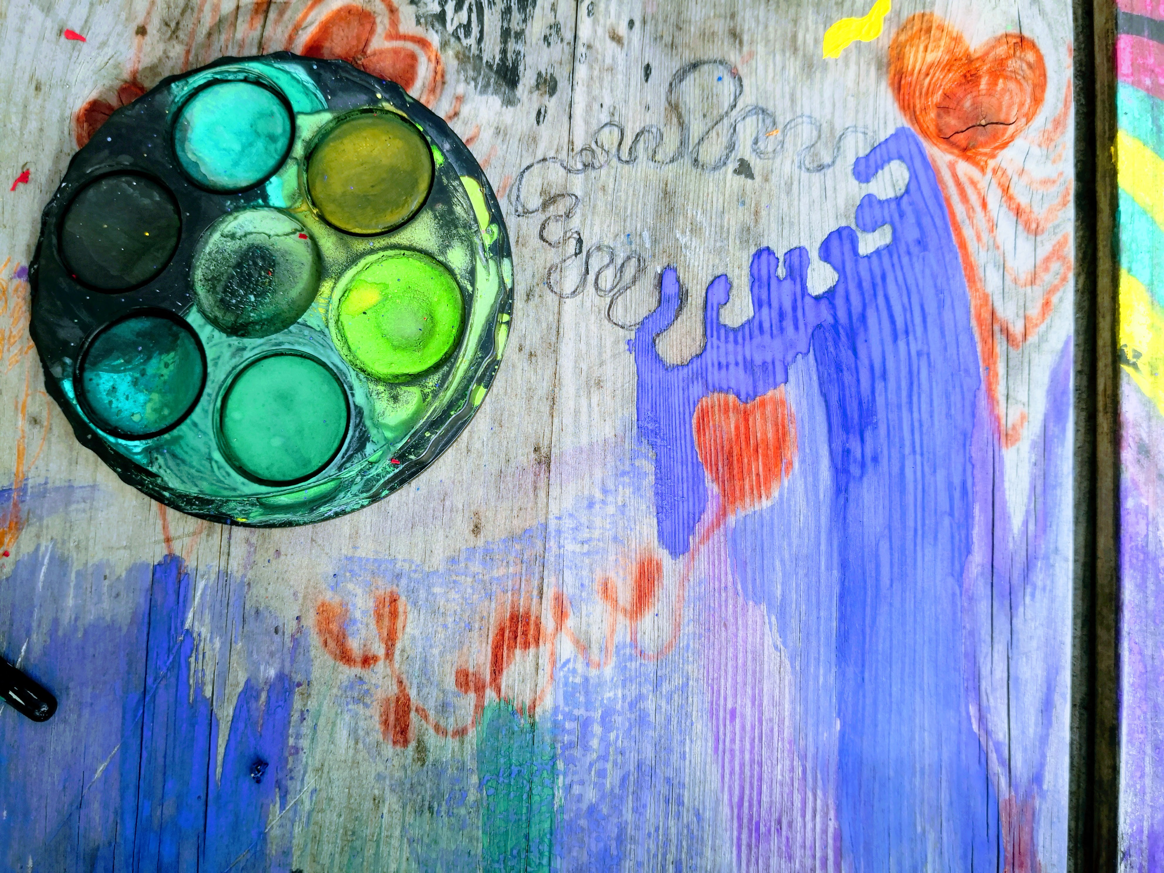 Paint pallet on wooden table covered with colourful paintings and doodles