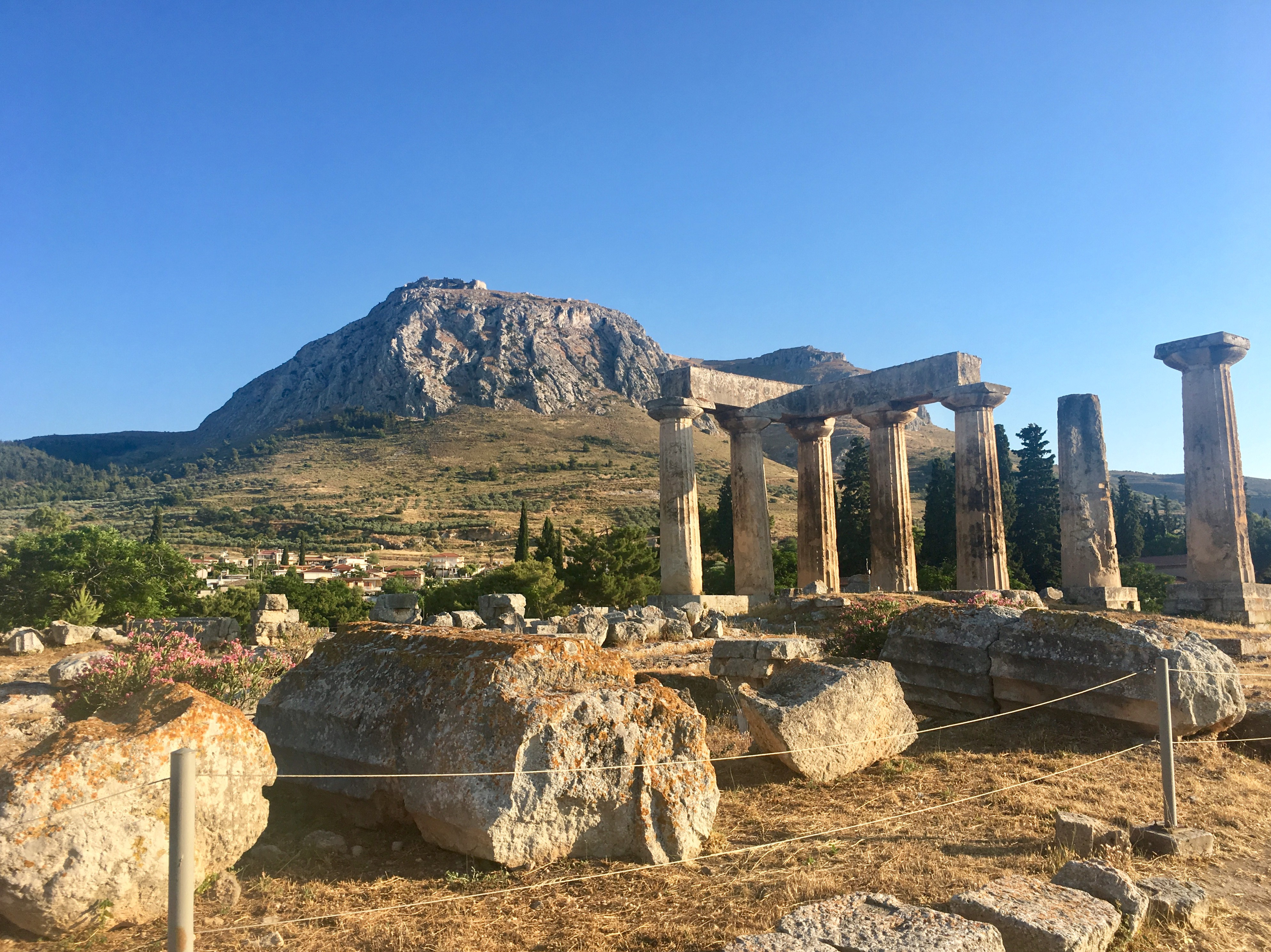 A shot of the Temple of Apollo in Corinth, with the mountain Acrocorinth behind it