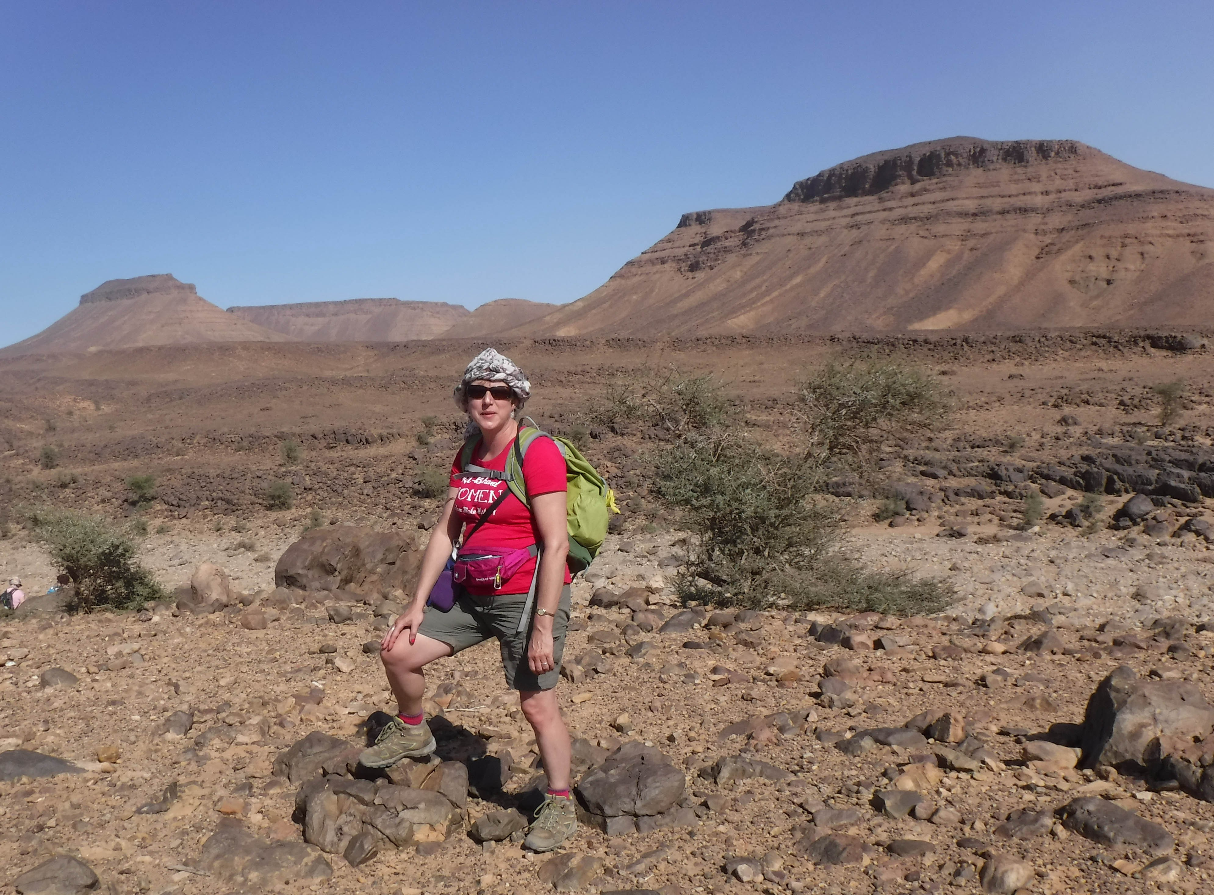 The author dressed in shorts and t-shirt with traditional desert headdress with rocky mountain back drop blue sky and hot