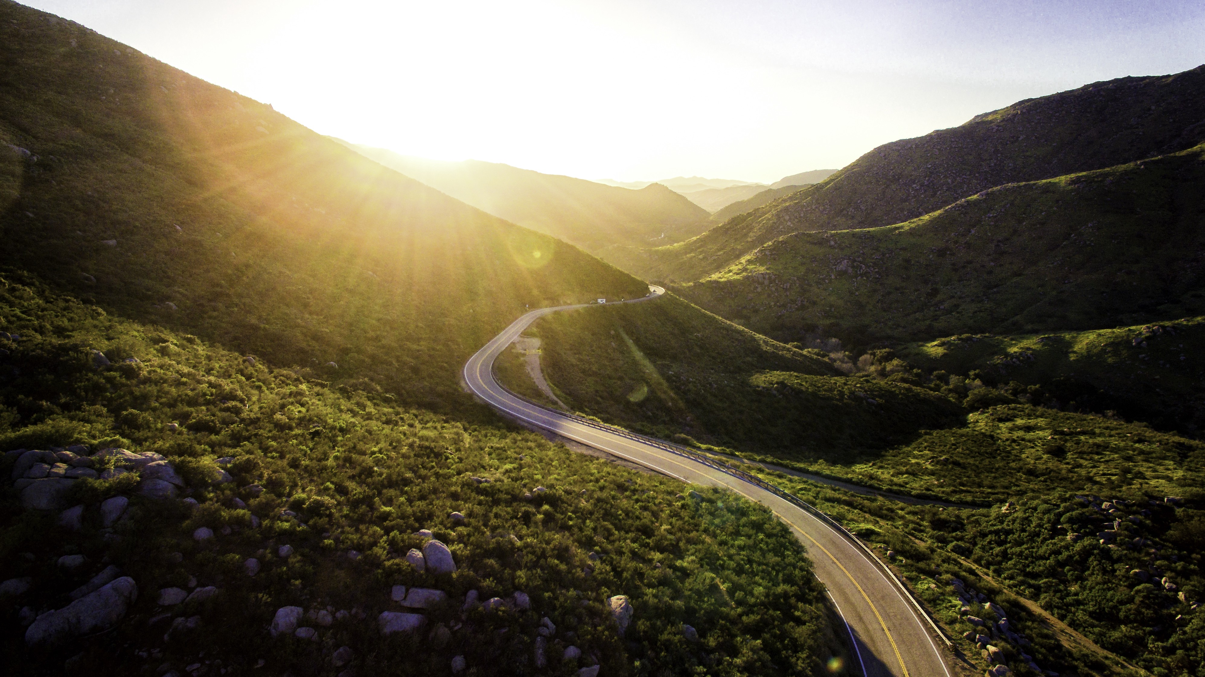 Winding road through sunlight hills and valleys