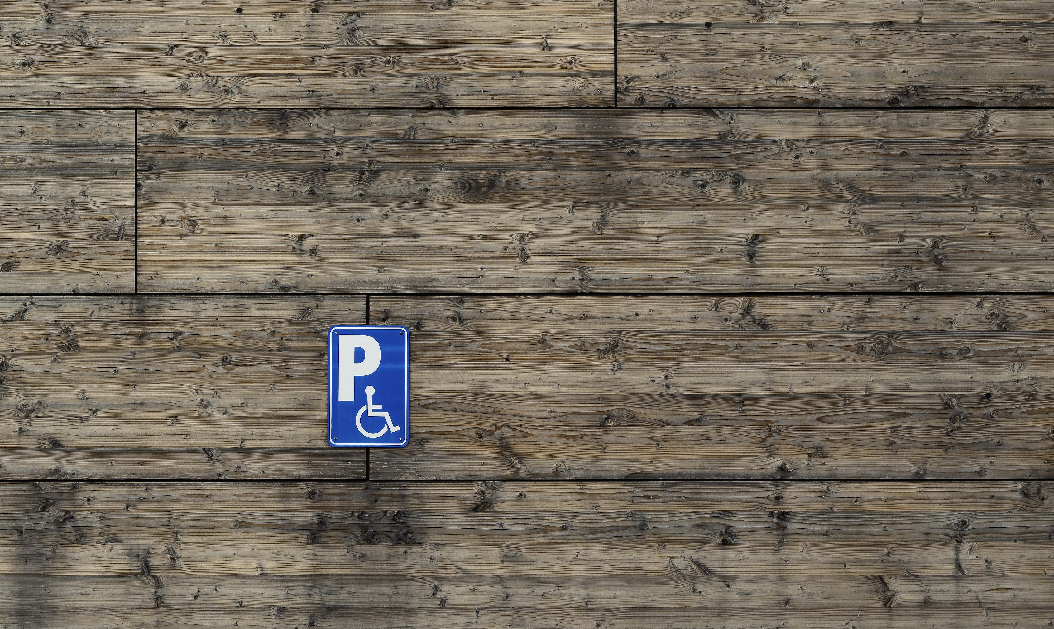 A decorative image for this article showing a disability-parking sign stuck on a wood/timber wall.