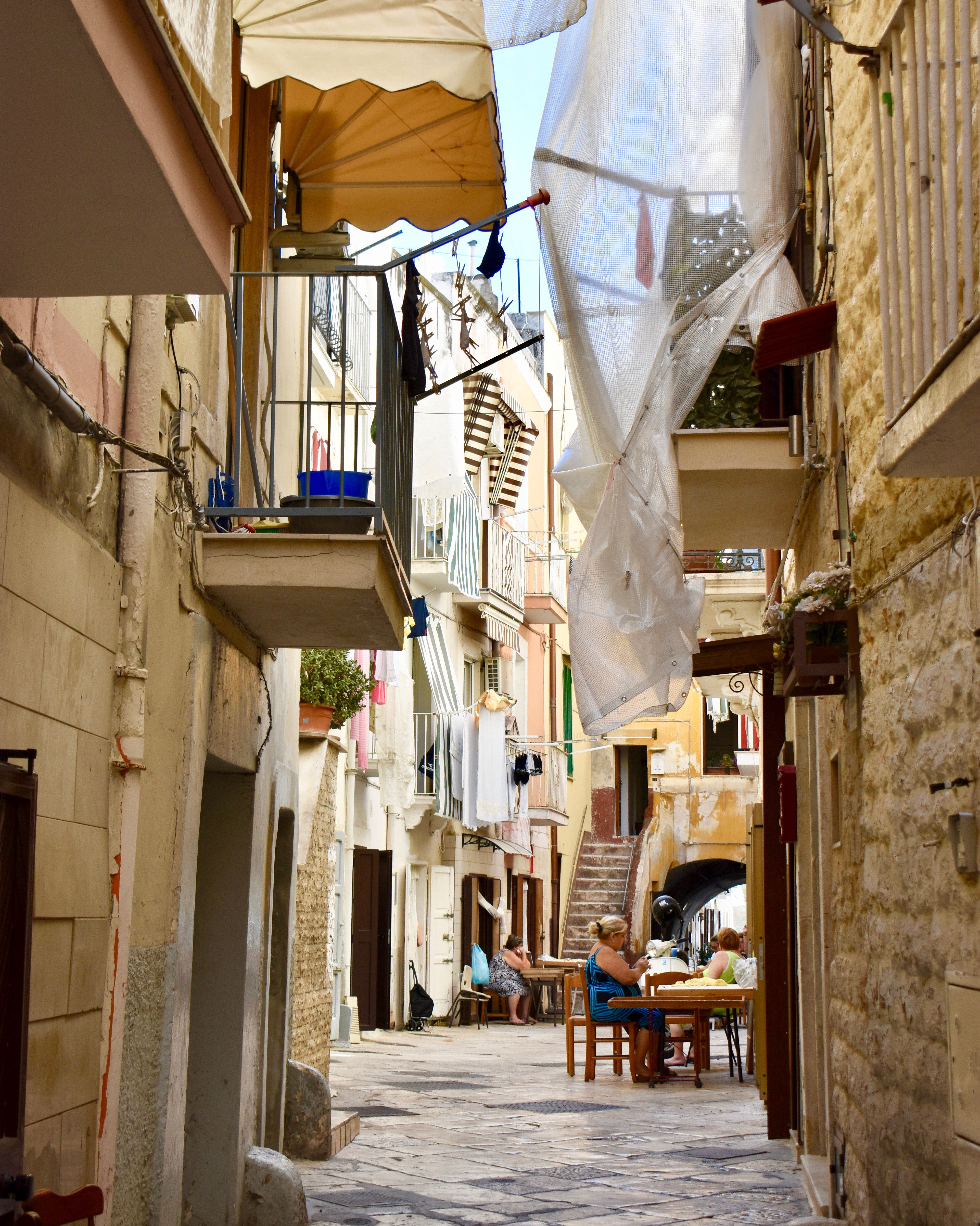 Vertical shot of a narrow alleyway with people working at tables at its far end.