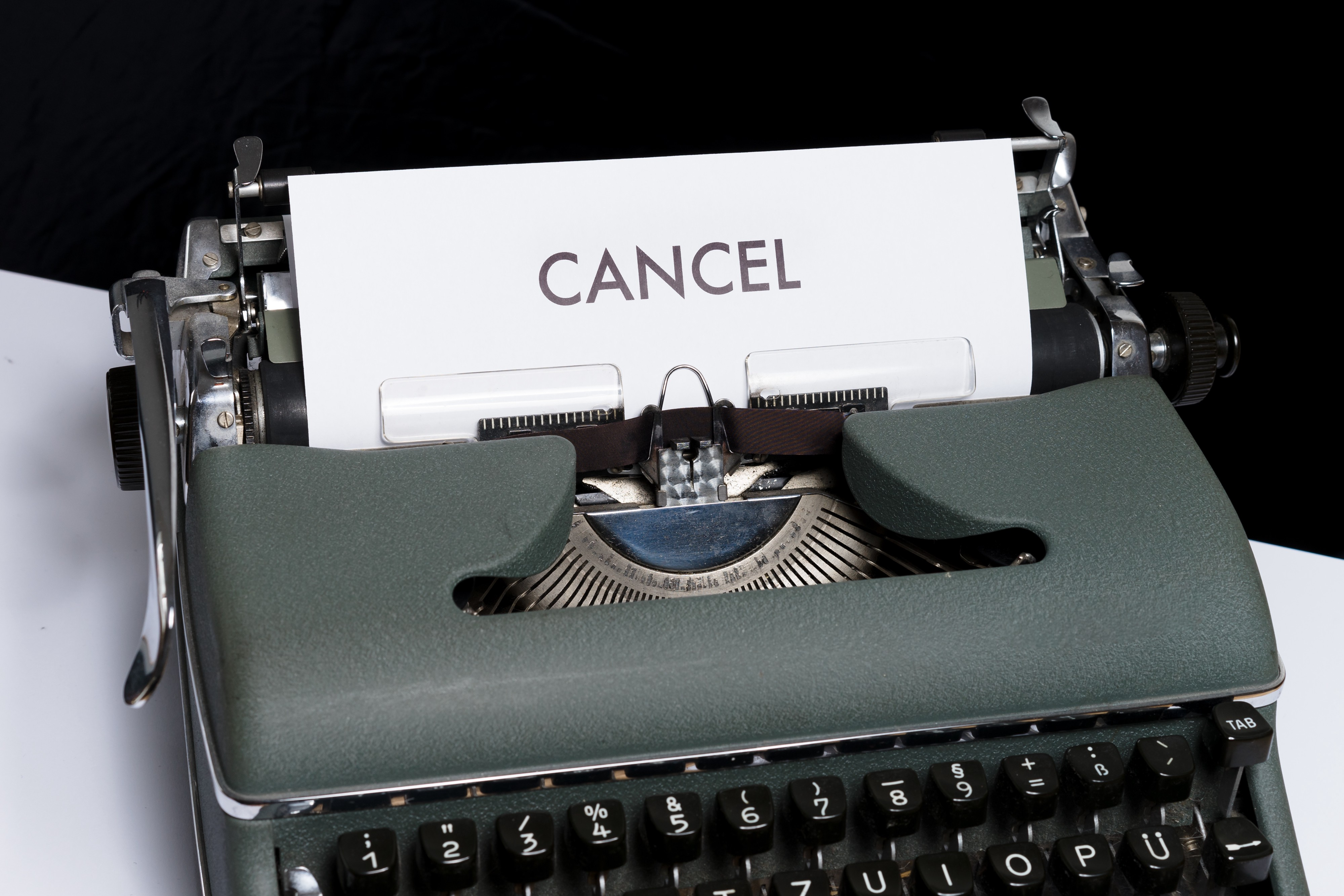 """Antique typewriter with a sheet of paper reading """"CANCEL"""""""