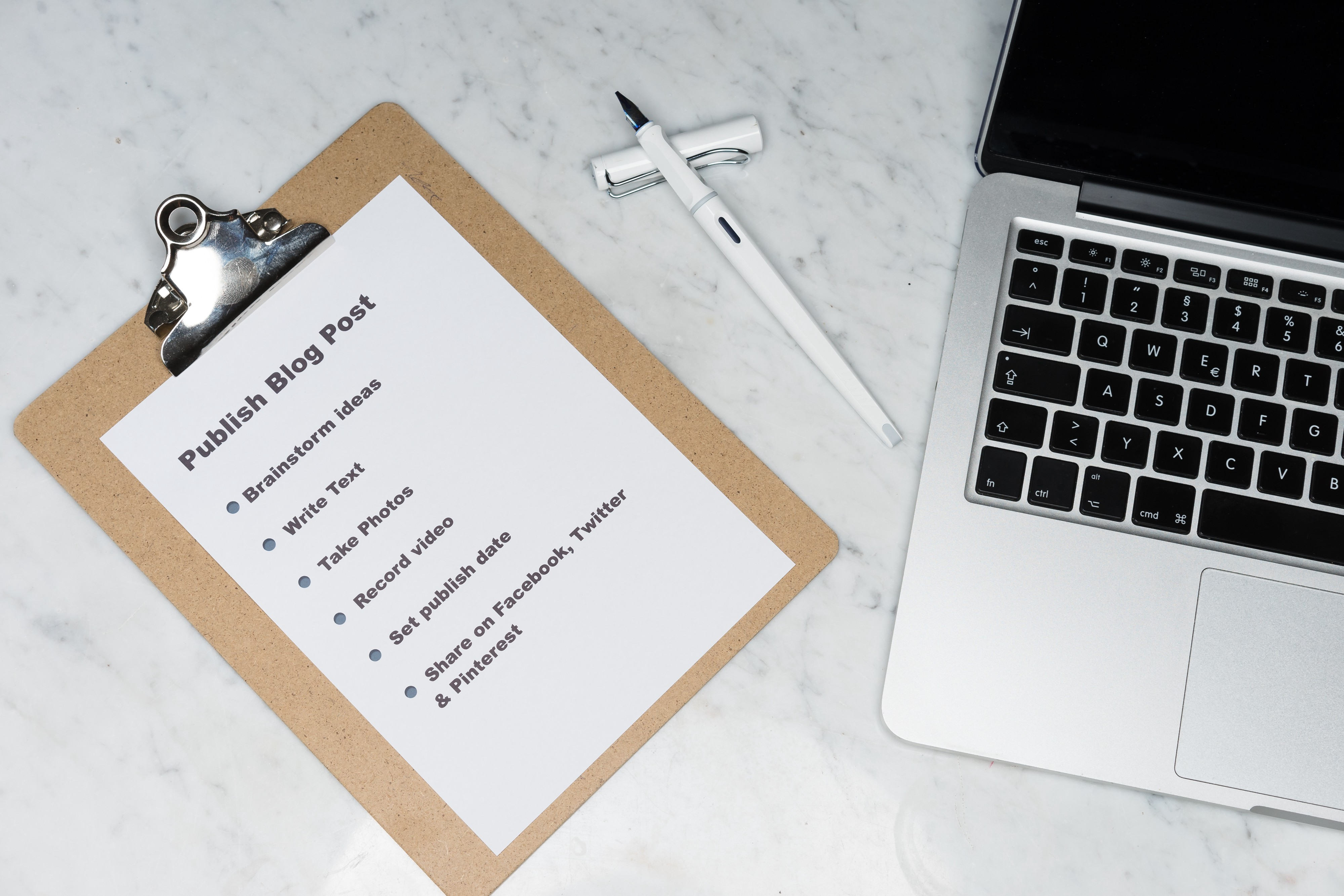 Image of a checklist for publishing a blog post with a pen and a Macbook