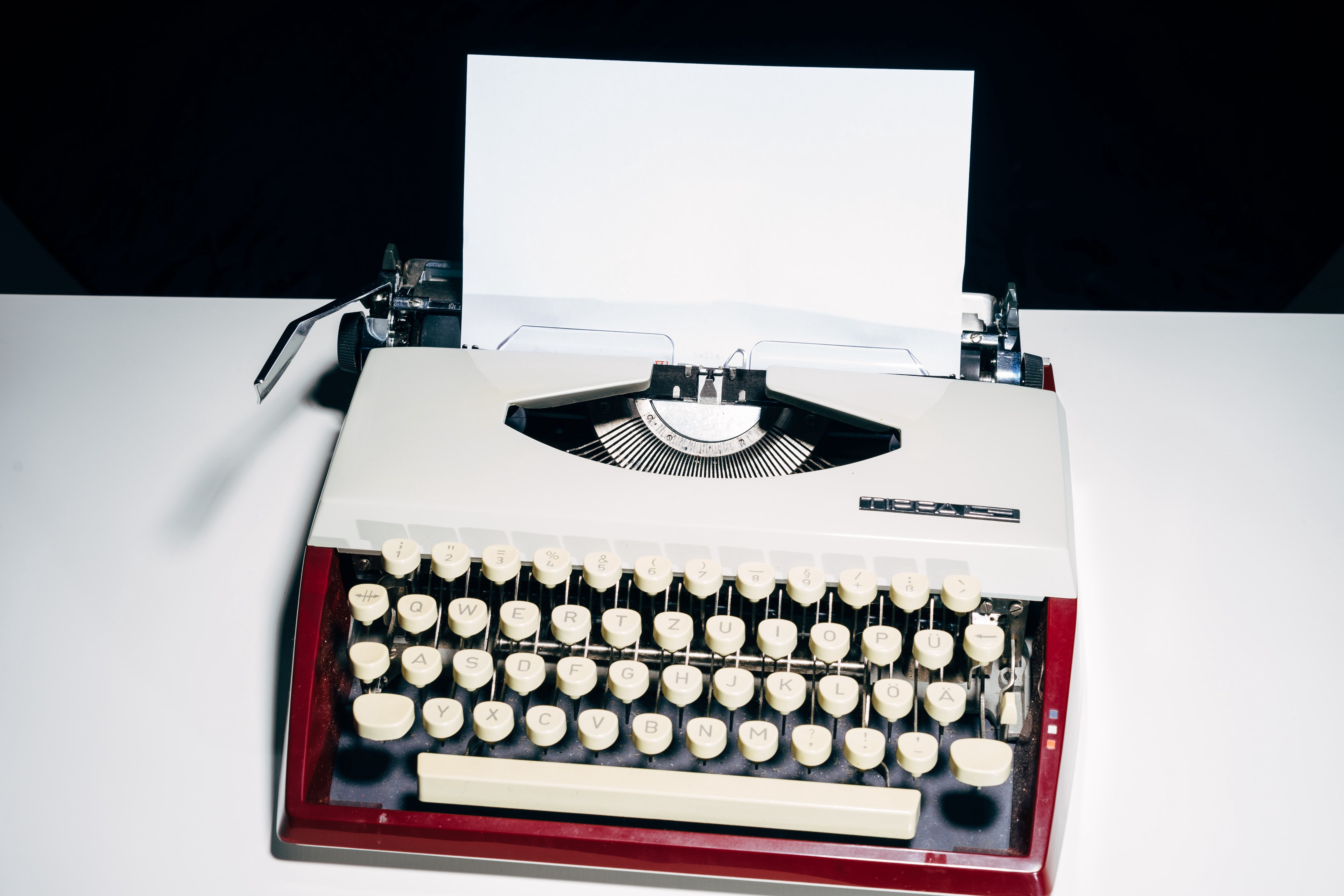 A manual typewriter with a sheet of blank paper in it.