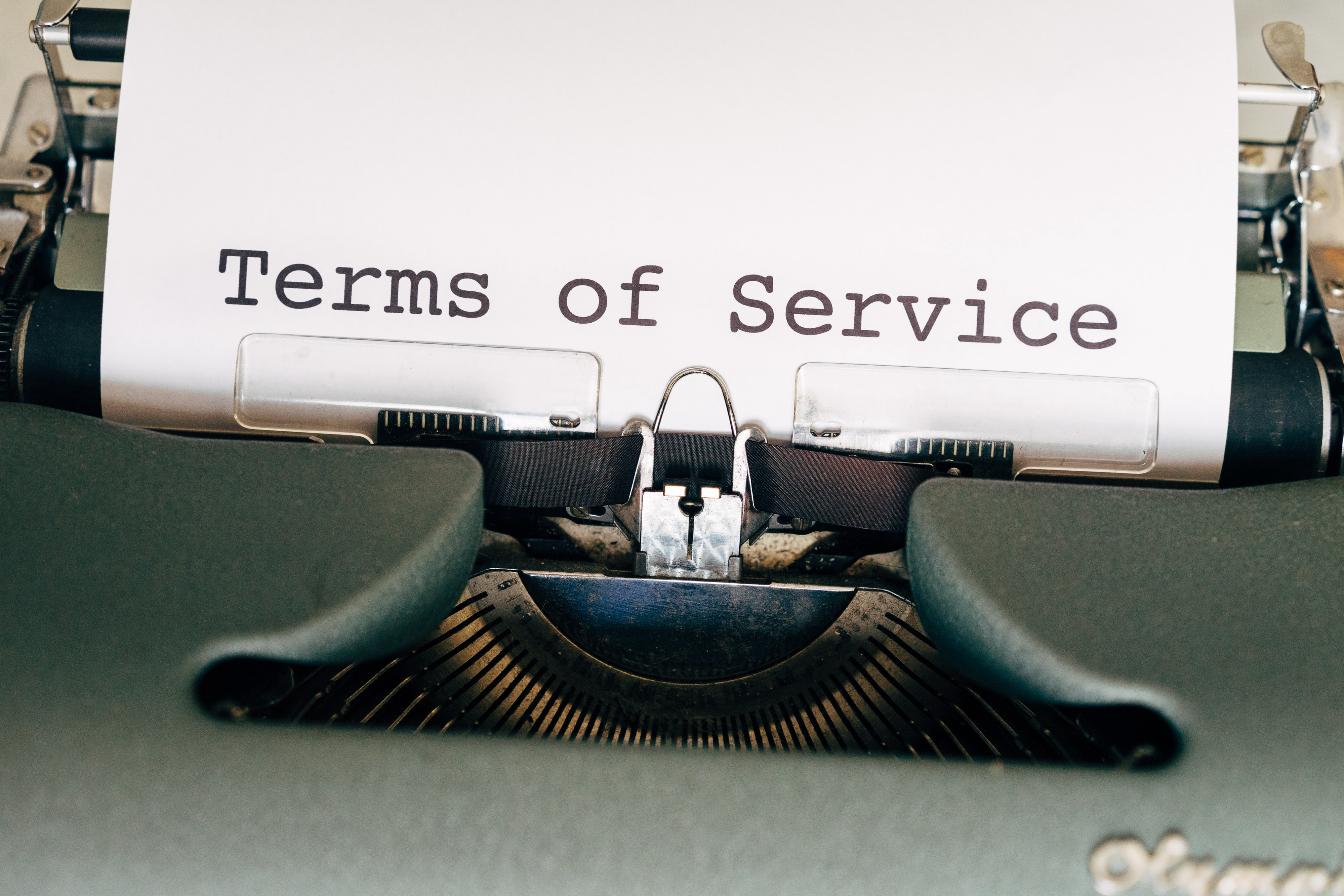 """typewriter with """"terms of service"""" written on paper coming out from it"""