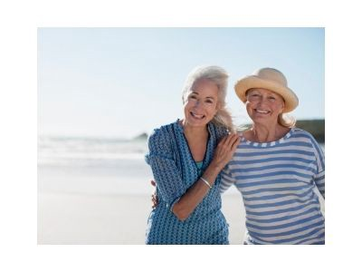Two senior women posing for a vacation picture on a beach.