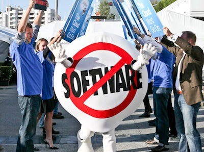 People protesting outside with anti-software slogans