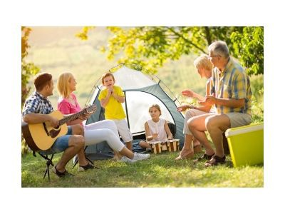 Family with three generations camping with man playing guitar