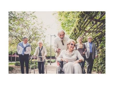 Three senior couples walking down a sunny street, one woman in a wheelchair.