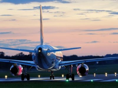 Rear view of a jet on a runway at sunset.