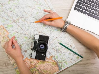 Image of map, camera, and laptop with hand holding pencil.
