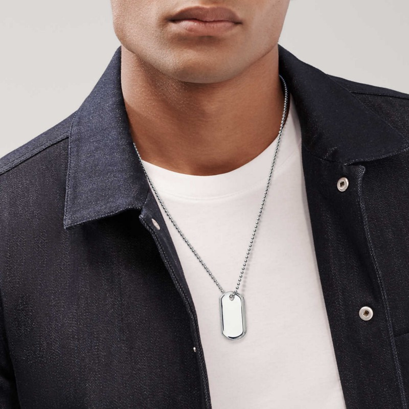 A man wearing a denim shirt layered on a white t-shirt with a silver dog tag visible. Strong chin, masculine, tanned.