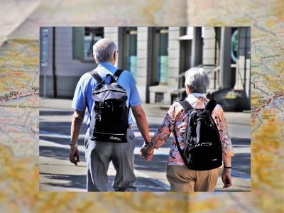 Rear view of a senior man and senior woman holding hands on vacation while wearing backpacks.