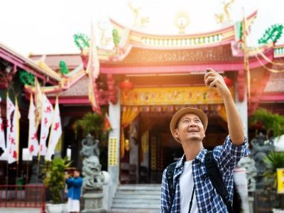 Senior man on vacation taking a selfie in front of a pagoda.