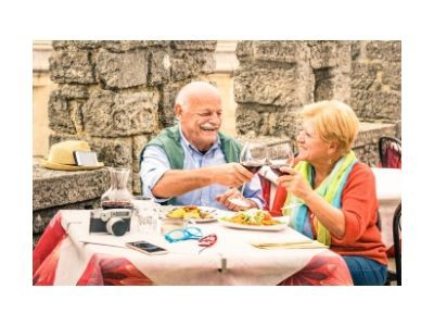 A senior couple toasting with wine at an outdoor cafe table