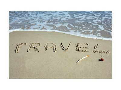Surf with the word travel written in the wet sand.