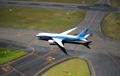 Plane on the runway at Sydney airport. The image has been tilt-shifted.