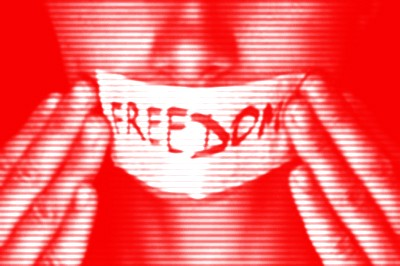 """Woman with paper pressed tightly over her mouth that reads """"freedom""""."""
