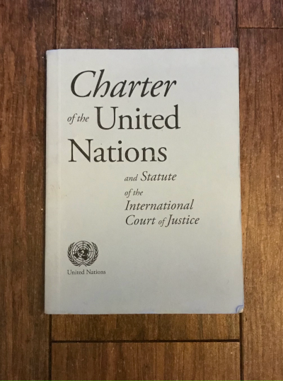 A small printed copy of the Charter of the United Nations sits on a wooden floor, and is viewed straight on.
