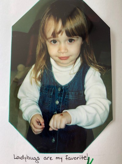 The author, Megan, as a 3-year-old holding a ladybug