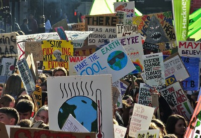 Placards with climate-related slogans and images of the Earth heating up