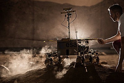A man guides a model rover over ground in a test center.