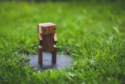 Wooden robot on a green lawn