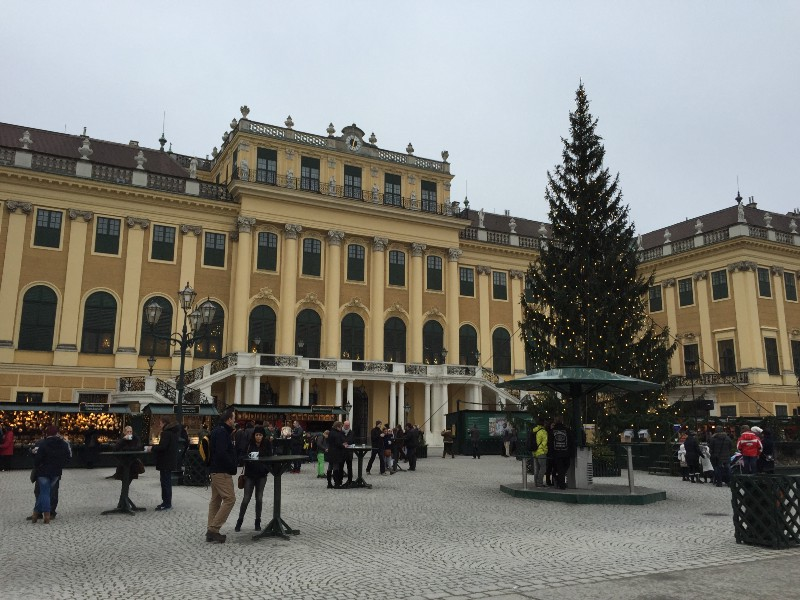 Schonbrunn Palace entrance. Christmas markets in front of the palace feeding hungry tourists with gluhwein, wursts, and waffles.