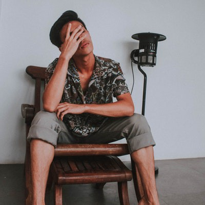 A man with black hair, sitting on a chair, alone, feeling stressed and sad.
