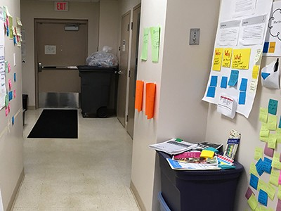 A service hallway filled with walls of Post-it notes and books on design thinking.