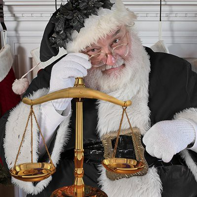 A picture of Emoluments Claus, a Santa Claus figure wearing all black robes holding the scales of justice.