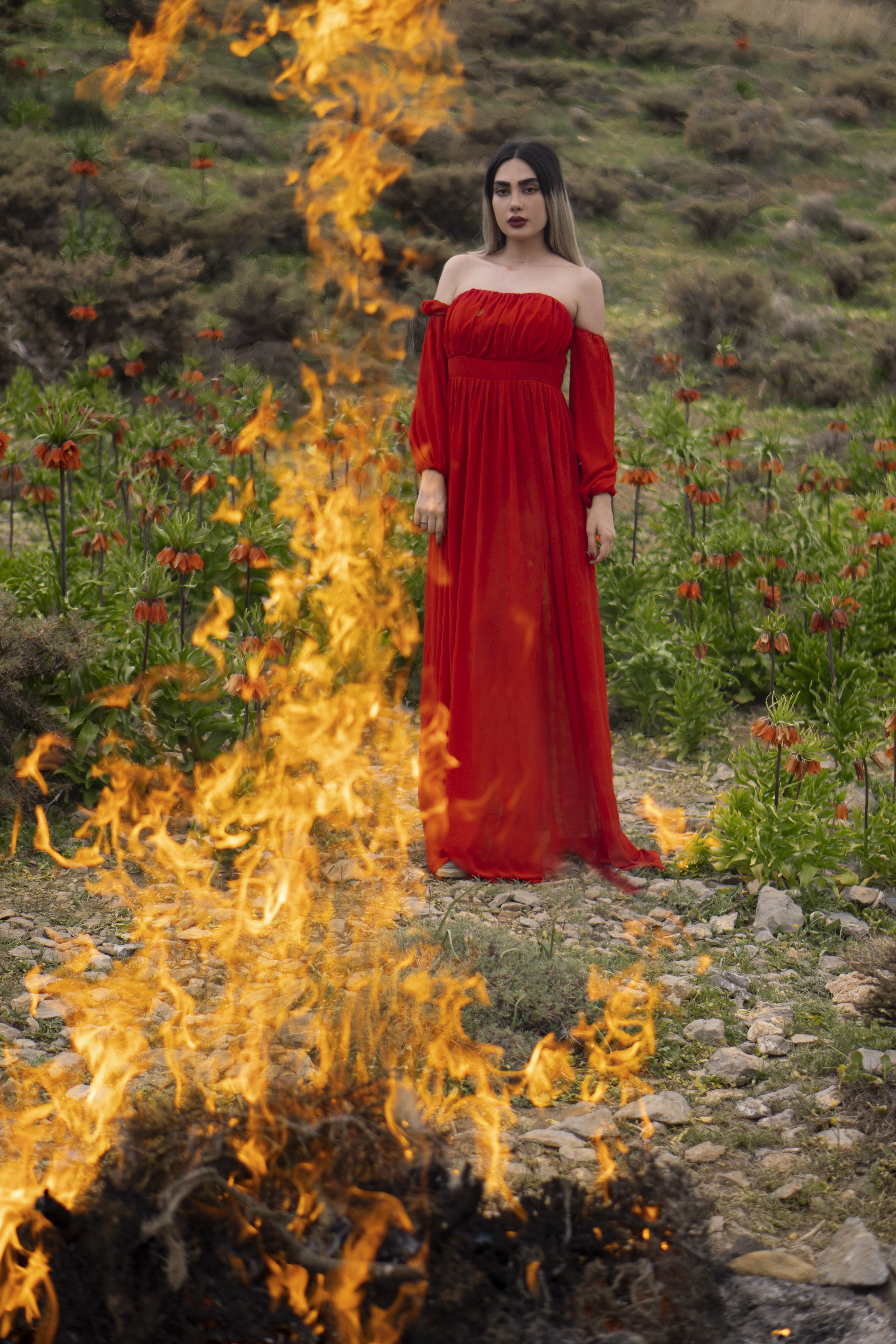 A woman in a red dress stands behind a fire in a field of red flowers.