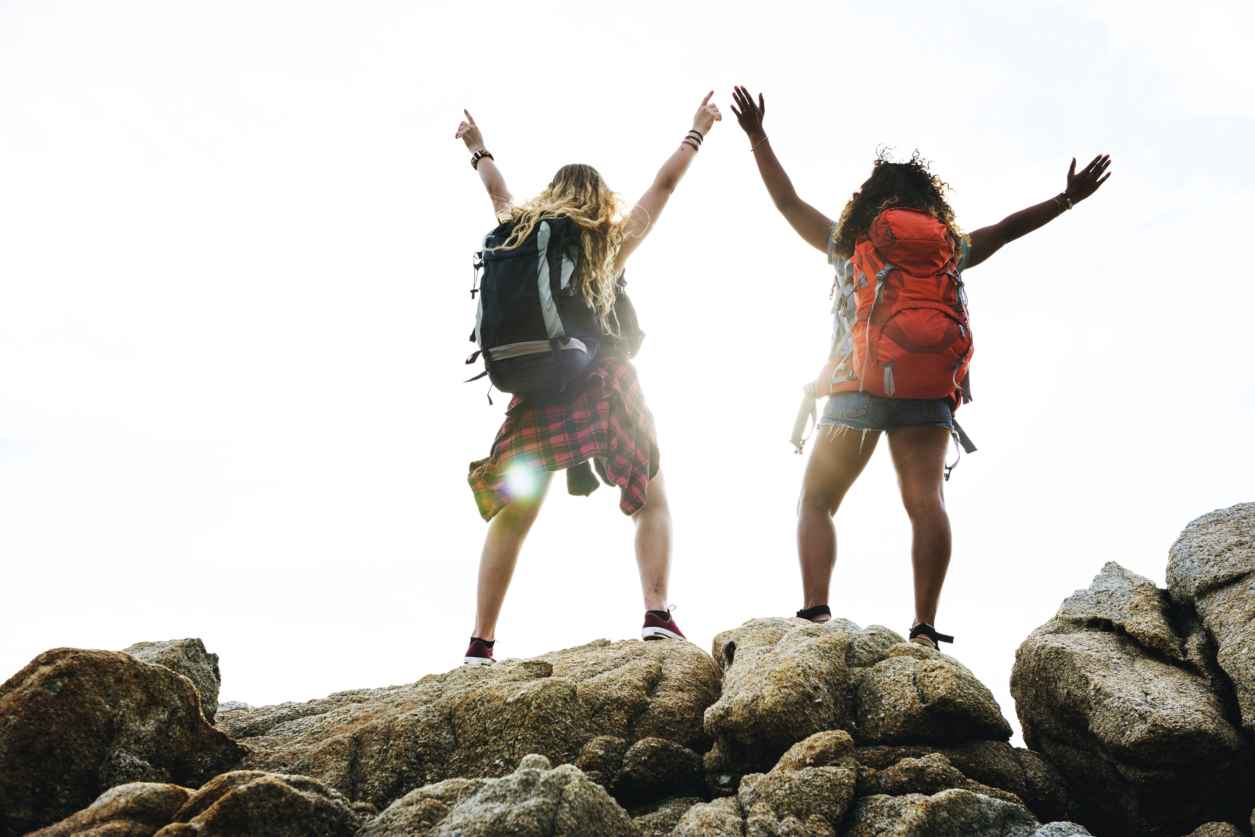 Two women in their 20's wearing backpacks stand triumphent at the top of a mountatin.