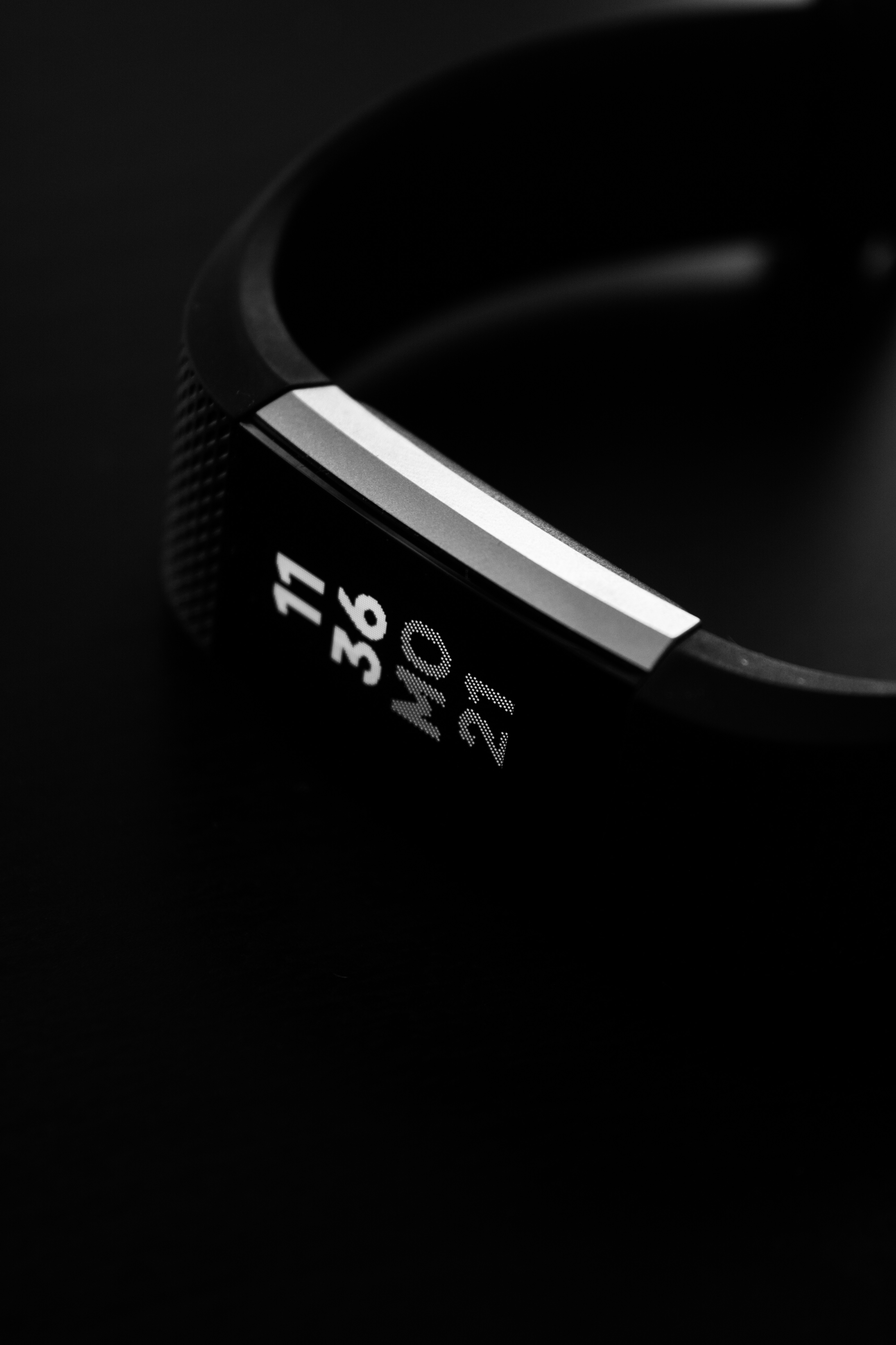 """A black Fitbit against a black background with silver details. The watch face reads """"11:36 MO 21."""""""