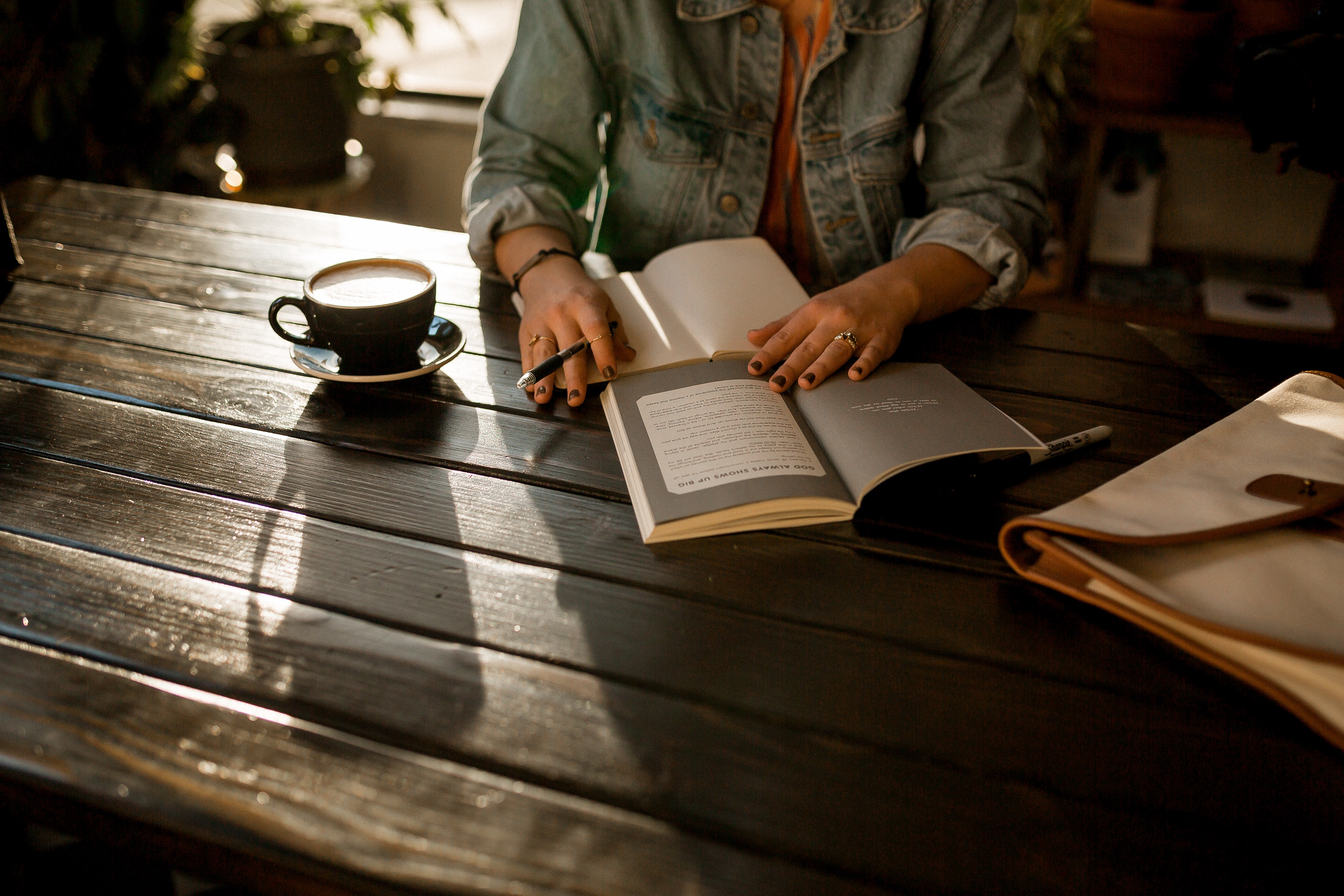 Woman with coffee and journals at table