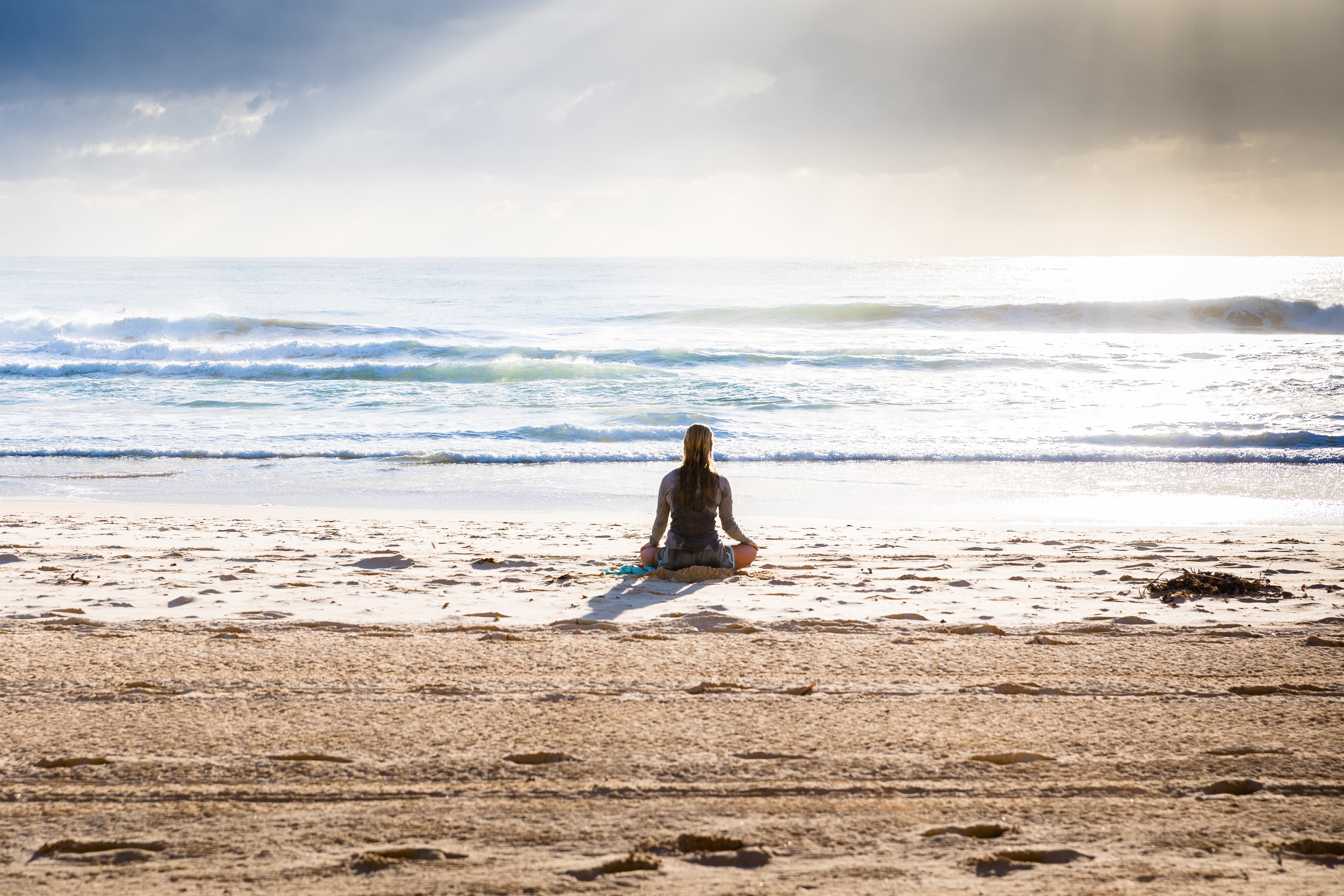 Person sitting on beach in a meditative pose.