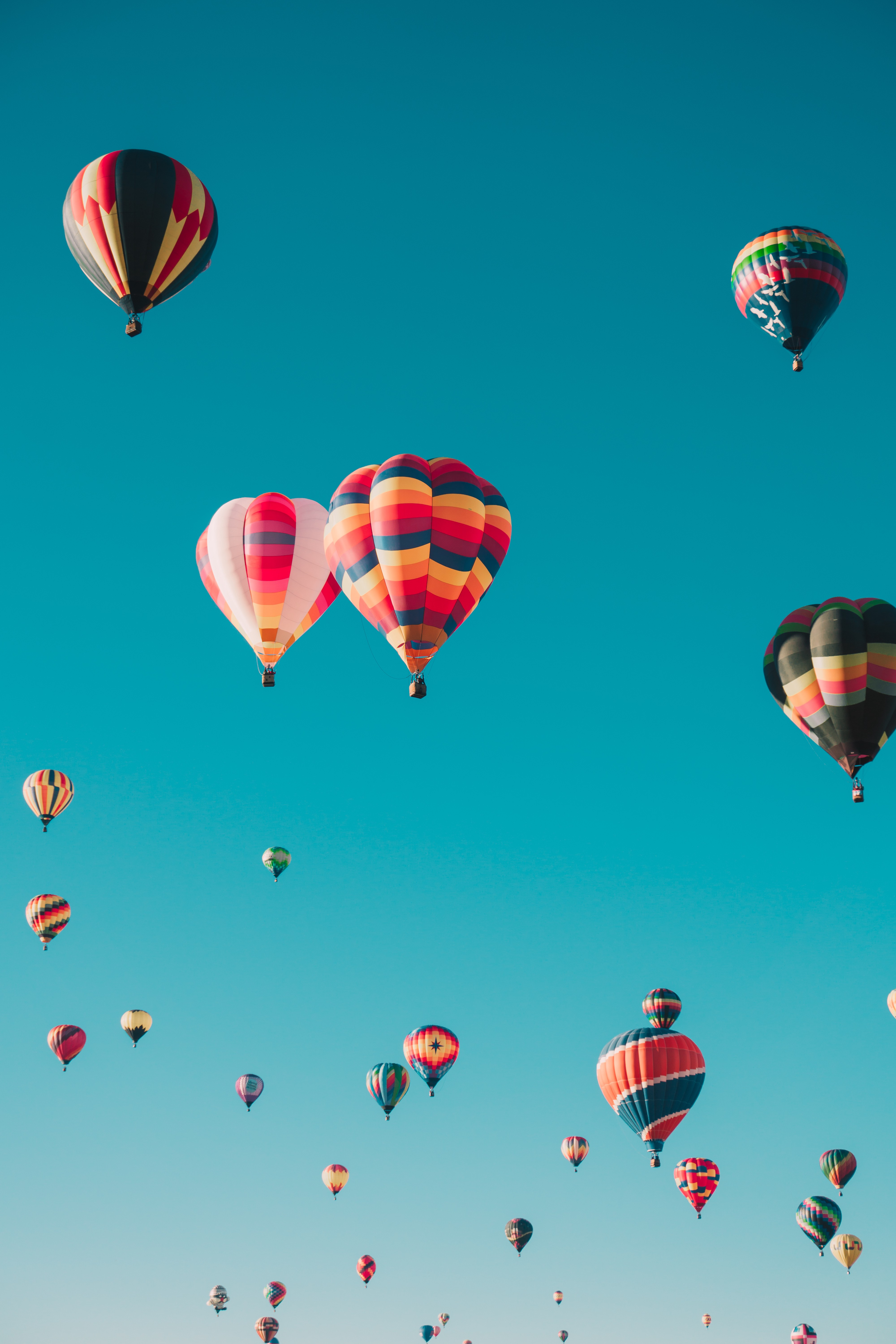 A blue sky with multiple hot air balloons flying in the air.