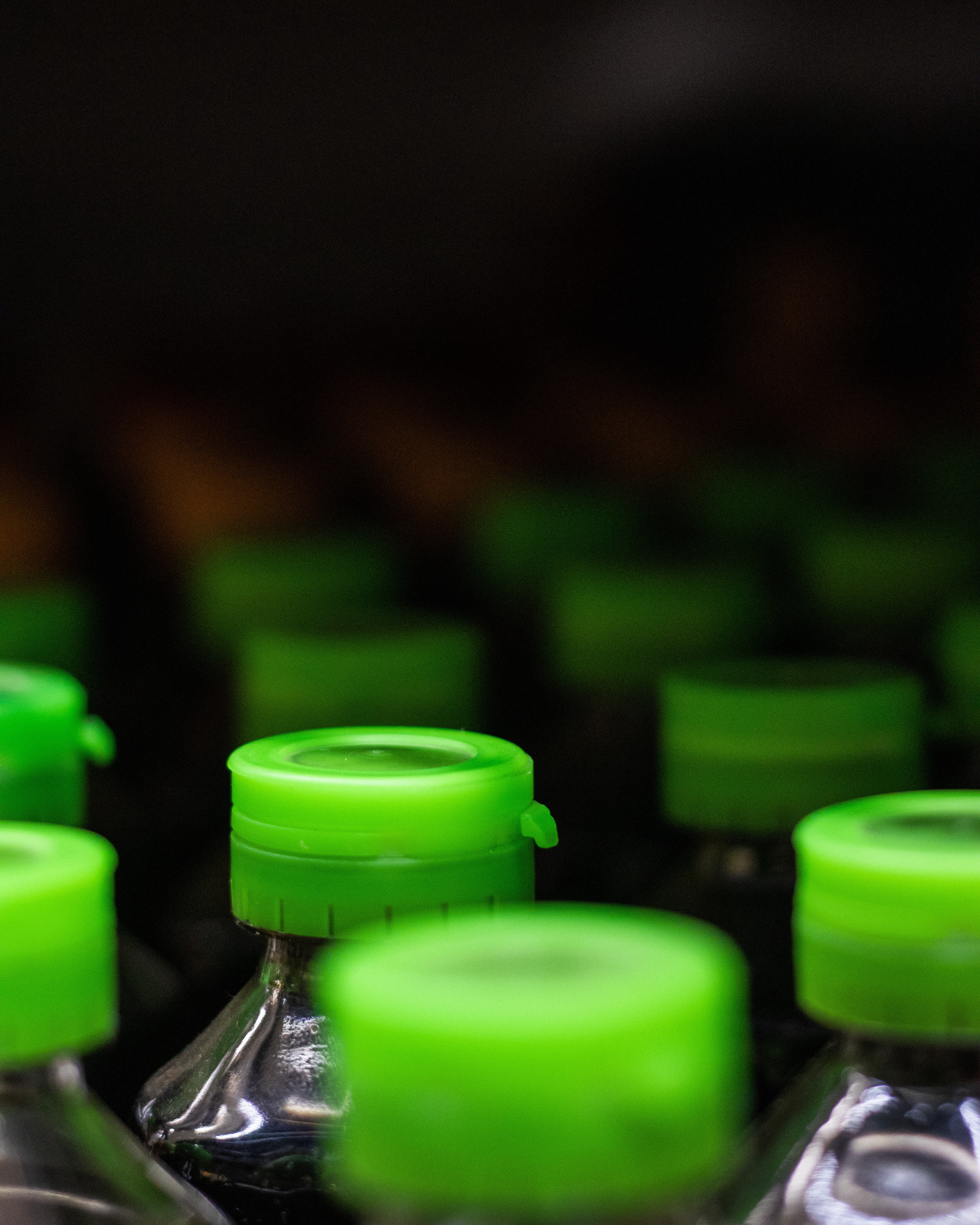 A group of plastic bottles, focusing on their bright green plastic caps.