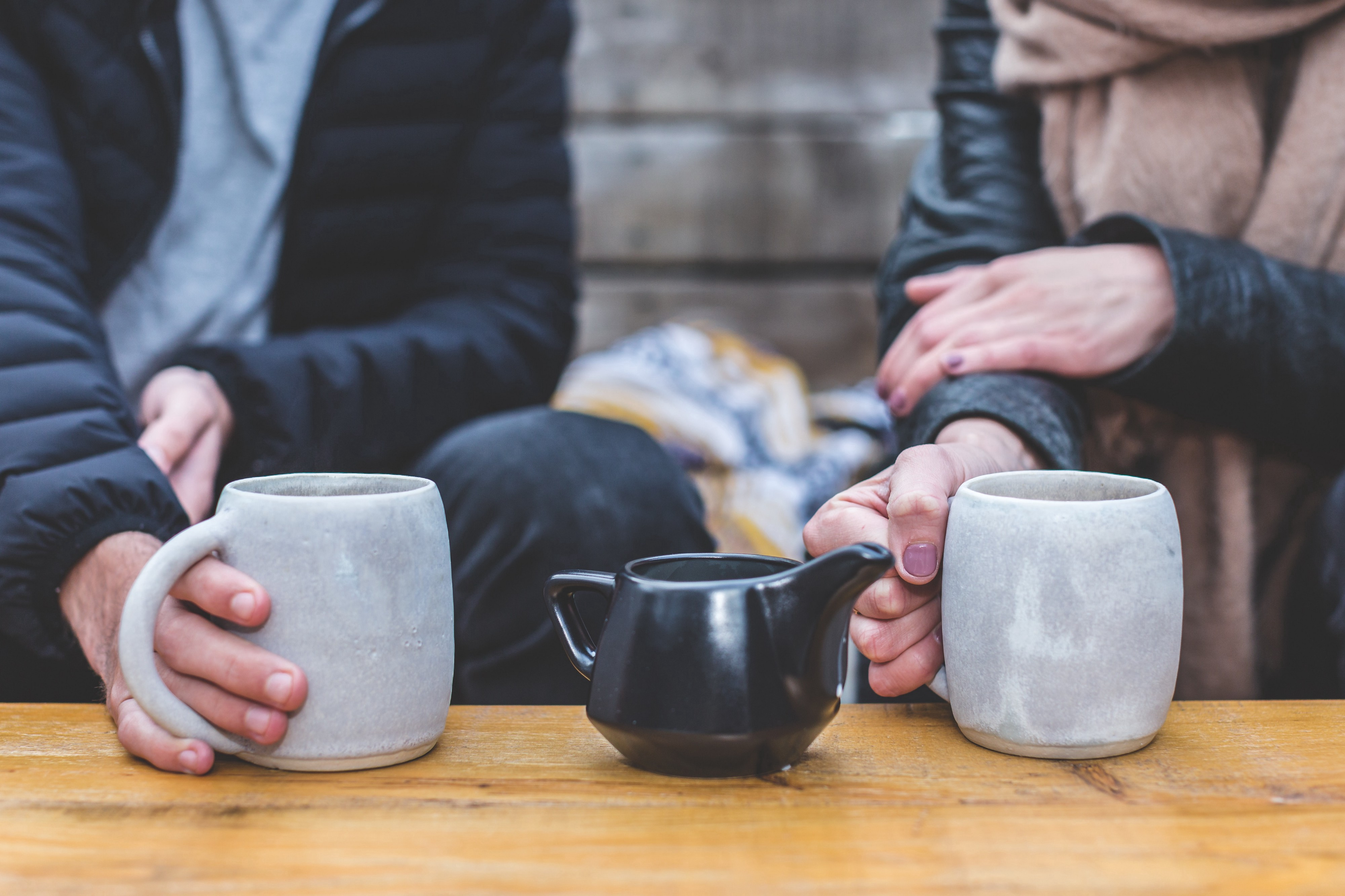 Two people wearing scarves and coats on a date, with a tea pot between two mugs of tea that they are holding.