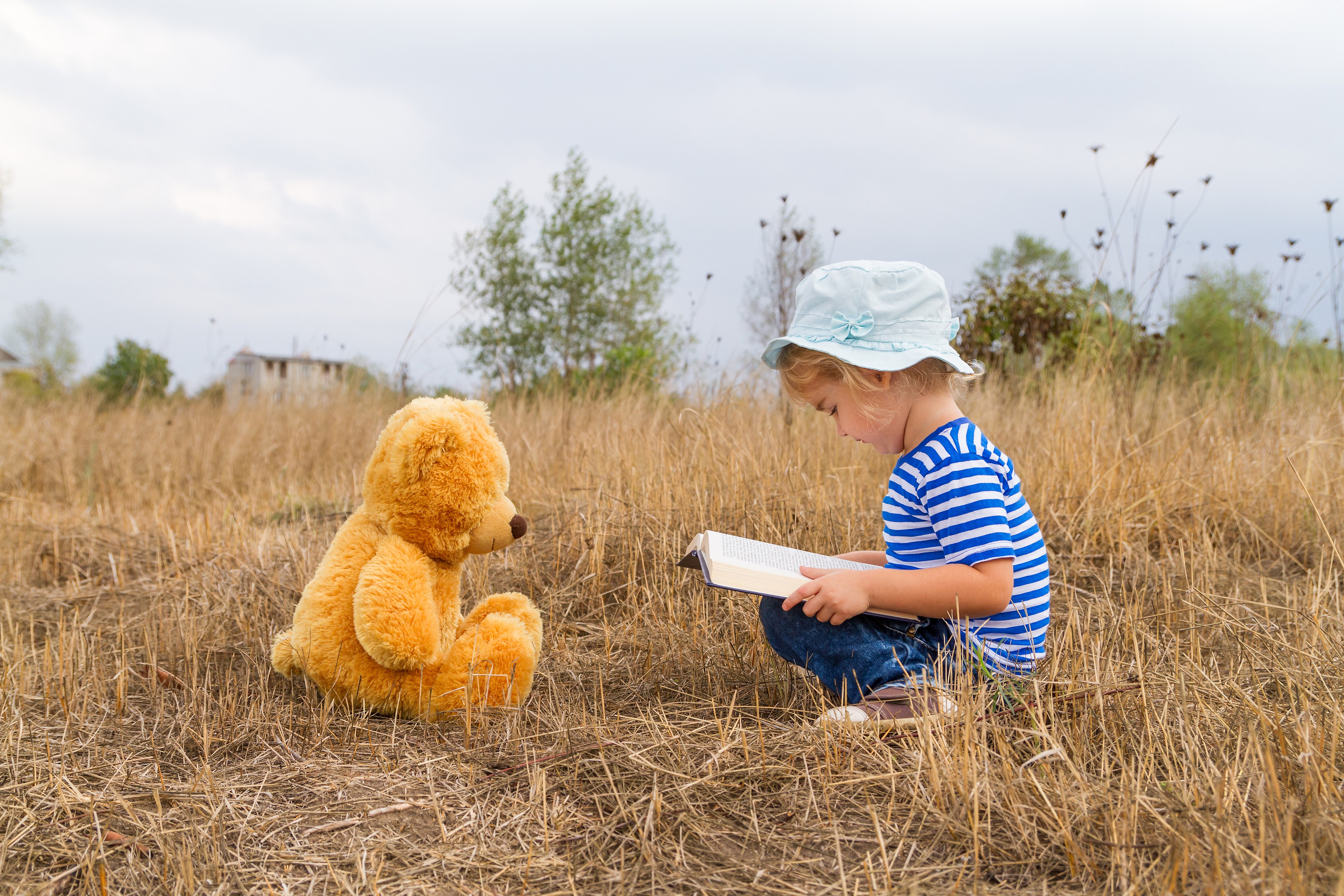 A child reading a story to her stuffed bear.
