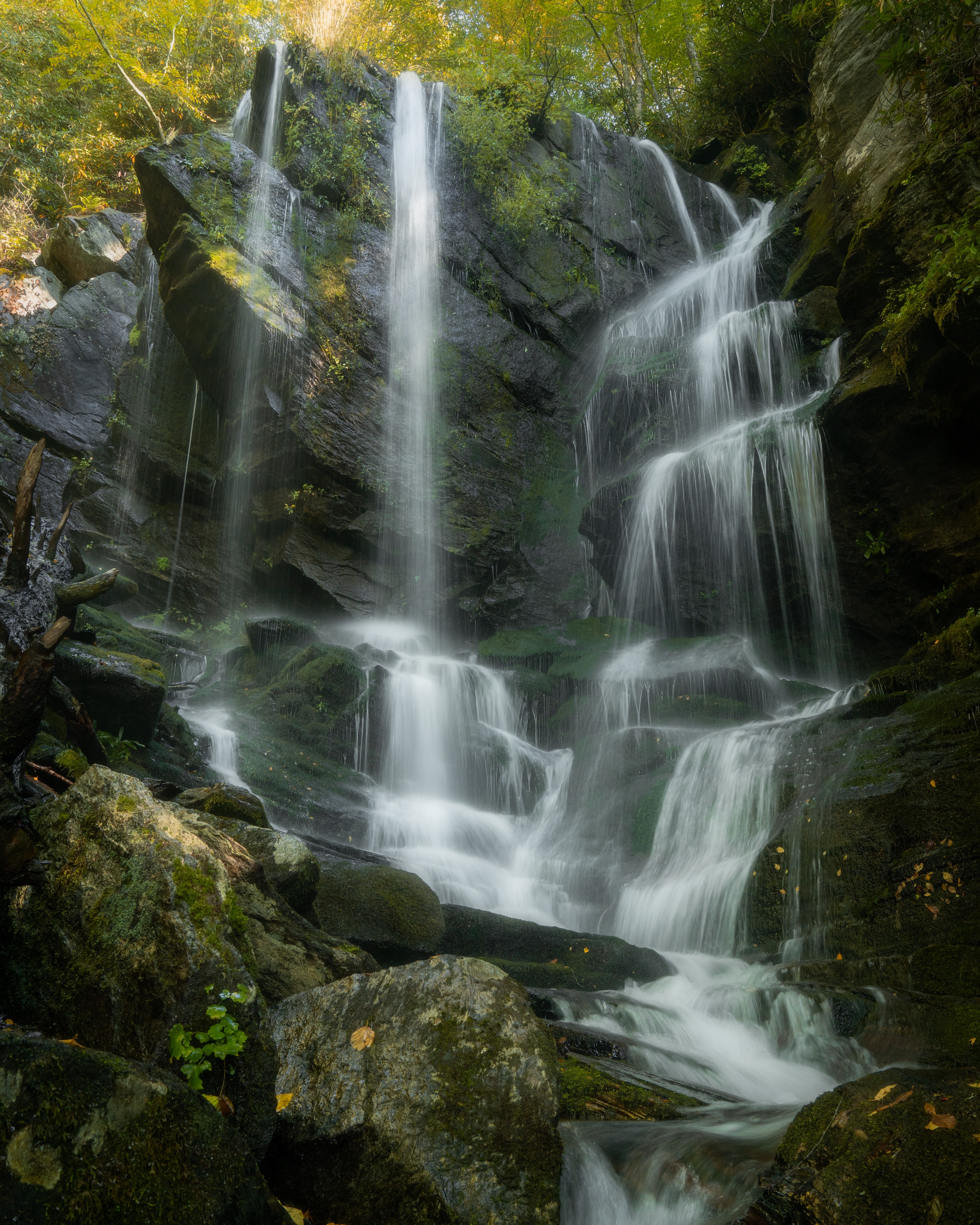 Waterfall cascading over mossy rocks in early morning light.