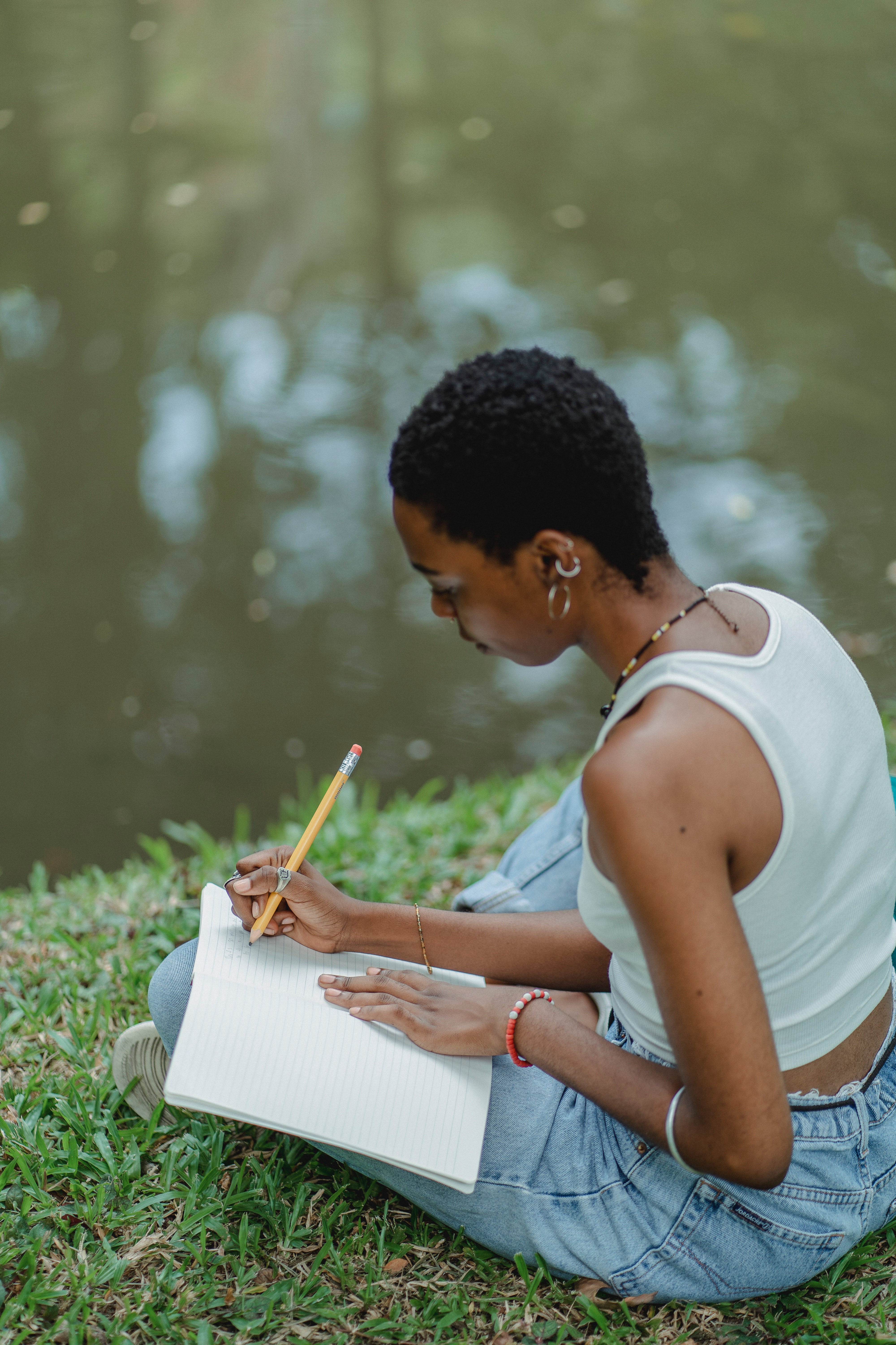 Black woman sitting cross legged and writing in a journal