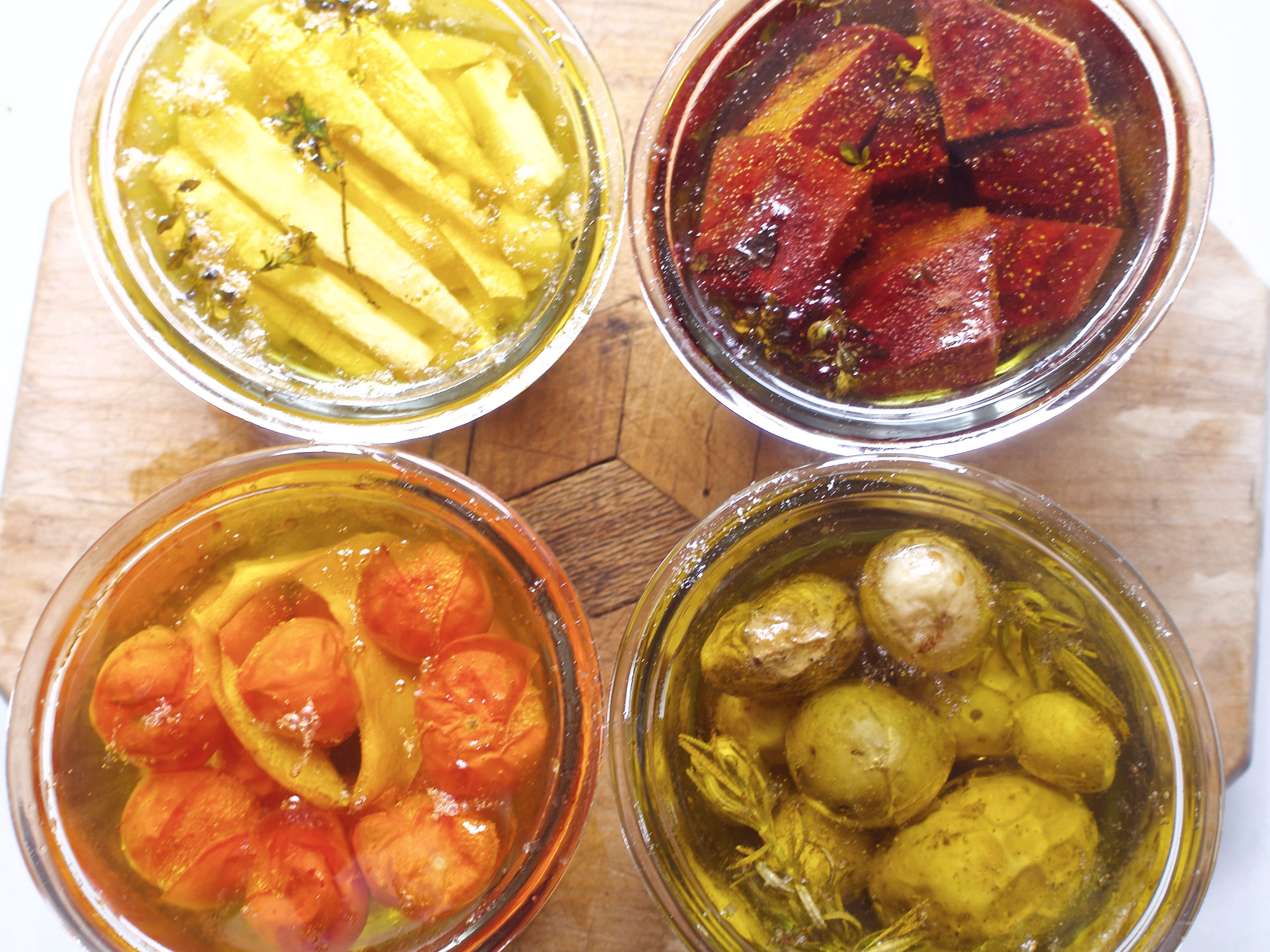four jars of oil and confit'd veg — parsnip, beet, tomato, and potatoes — in rich color