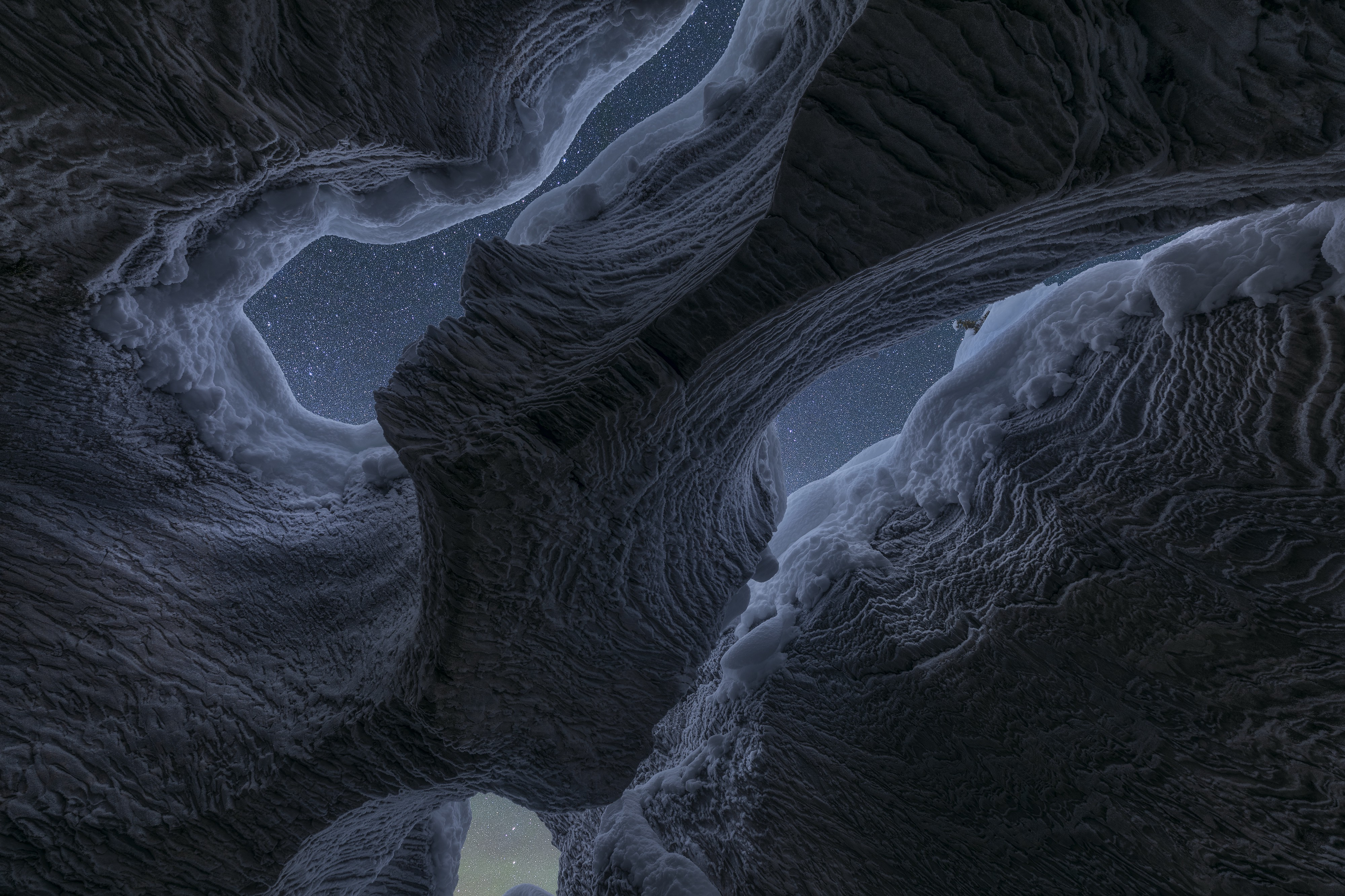 A night-lit shot of the Rocky Mountains, showing a cave texture that looks like water or art